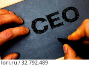Word writing text Ceo. Business concept for Chief Executive Officer Head Boss Chairperson Chairman Controller Man hold holding black marker markers notebook wood wooden background. Стоковое фото, фотограф Zoonar.com/Artur Szczybylo / easy Fotostock / Фотобанк Лори
