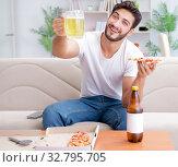 Купить «Man eating pizza having a takeaway at home relaxing resting», фото № 32795705, снято 18 июля 2017 г. (c) Elnur / Фотобанк Лори