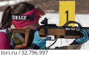 Biathlete aiming, rifle shooting in prone position. Sportswoman biathlete Ivchenko Anastasia in shooting range. Junior biathlon competitions East of Cup (2019 год). Редакционное видео, видеограф А. А. Пирагис / Фотобанк Лори