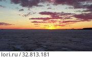 Купить «Flying over frozen sea at amazing sunset with red Sun and clouds», видеоролик № 32813181, снято 22 декабря 2019 г. (c) Serg Zastavkin / Фотобанк Лори