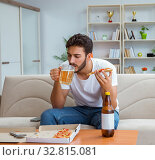 Купить «Man eating pizza having a takeaway at home relaxing resting», фото № 32815081, снято 18 июля 2017 г. (c) Elnur / Фотобанк Лори