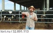 Купить «Smiling man farmer standing near cow on background at farm outdoor», видеоролик № 32891113, снято 9 июня 2019 г. (c) Яков Филимонов / Фотобанк Лори