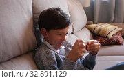 Купить «Boy looking to smartphone screen on sofa in domestic interior», видеоролик № 32891129, снято 12 июня 2019 г. (c) Яков Филимонов / Фотобанк Лори