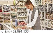 Купить «Confident salesgirl offering colored buttons for dressmaking in sewing supplies shop», видеоролик № 32891133, снято 4 апреля 2020 г. (c) Яков Филимонов / Фотобанк Лори