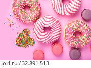 Купить «Donuts and macaroons on a pink background.», фото № 32891513, снято 3 ноября 2018 г. (c) Елена Блохина / Фотобанк Лори