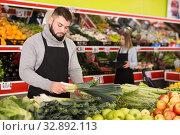 Купить «Male shop assistant lays fresh leek on counter in grocery shop», фото № 32892113, снято 20 ноября 2019 г. (c) Яков Филимонов / Фотобанк Лори