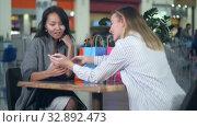 Купить «Happy asian woman looking at a new dress, her blond friend take photo of her in shopping mall», видеоролик № 32892473, снято 26 июня 2017 г. (c) Vasily Alexandrovich Gronskiy / Фотобанк Лори