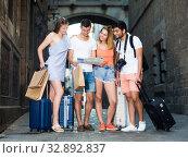 Купить «Young happy people searching for direction using paper map», фото № 32892837, снято 22 июня 2017 г. (c) Яков Филимонов / Фотобанк Лори