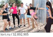 Купить «Girl practicing pole exercises on beach», фото № 32892905, снято 14 июня 2017 г. (c) Яков Филимонов / Фотобанк Лори