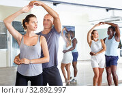 Купить «Young smiling people practicing passionate samba in dance class», фото № 32892997, снято 30 июля 2018 г. (c) Яков Филимонов / Фотобанк Лори