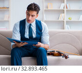 Купить «Young musician man practicing playing violin at home», фото № 32893465, снято 15 августа 2017 г. (c) Elnur / Фотобанк Лори