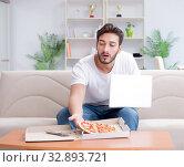 Купить «Man eating pizza having a takeaway at home relaxing resting», фото № 32893721, снято 18 июля 2017 г. (c) Elnur / Фотобанк Лори
