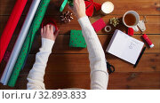 hands wrapping christmas gift and writing note. Стоковое видео, видеограф Syda Productions / Фотобанк Лори