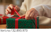Купить «hands packing christmas gift and tying bow», видеоролик № 32893973, снято 18 декабря 2019 г. (c) Syda Productions / Фотобанк Лори
