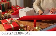 Купить «hands wrapping christmas gift into paper at home», видеоролик № 32894045, снято 18 декабря 2019 г. (c) Syda Productions / Фотобанк Лори