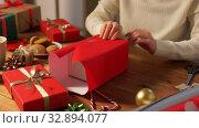 Купить «woman wrapping christmas gift into paper at home», видеоролик № 32894077, снято 18 декабря 2019 г. (c) Syda Productions / Фотобанк Лори
