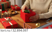 Купить «woman wrapping christmas gift into paper at home», видеоролик № 32894097, снято 18 декабря 2019 г. (c) Syda Productions / Фотобанк Лори