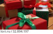 Купить «hands stacking packed christmas gifts on table», видеоролик № 32894197, снято 18 декабря 2019 г. (c) Syda Productions / Фотобанк Лори