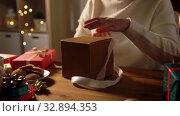 Купить «woman opening christmas gift at home», видеоролик № 32894353, снято 18 декабря 2019 г. (c) Syda Productions / Фотобанк Лори