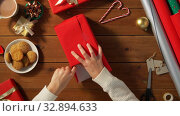 woman wrapping christmas gift into paper at home. Стоковое видео, видеограф Syda Productions / Фотобанк Лори