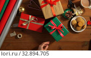 Купить «hands stacking packed christmas gifts on table», видеоролик № 32894705, снято 18 декабря 2019 г. (c) Syda Productions / Фотобанк Лори