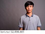 Studio shot of young Asian man wearing gray polo shirt against gray background. Стоковое фото, фотограф Zoonar.com/Toni Rantala / easy Fotostock / Фотобанк Лори