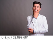 Studio shot of young Asian businessman wearing white shirt against gray background. Стоковое фото, фотограф Zoonar.com/Toni Rantala / easy Fotostock / Фотобанк Лори