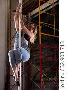 Купить «Young woman in ripped jeans performing pole dance», фото № 32903713, снято 6 июля 2020 г. (c) Яков Филимонов / Фотобанк Лори