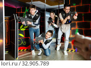 Ordinary Laser tag players young mens and womens playing in teams in dark laser tag station. Стоковое фото, фотограф Яков Филимонов / Фотобанк Лори