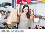 smiling young brunette with bags in footwear shop. Стоковое фото, фотограф Яков Филимонов / Фотобанк Лори