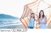 Купить «Mom with a small daughter walks along the beach with an umbrella on a sunny summer day.», фото № 32906237, снято 18 июля 2019 г. (c) Акиньшин Владимир / Фотобанк Лори