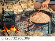 Купить «A young man cooks outdoors pilaf in a cauldron at the stake.», фото № 32906309, снято 19 июля 2019 г. (c) Акиньшин Владимир / Фотобанк Лори