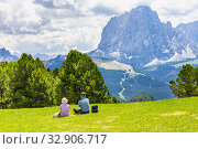 Two elderly people seen at Seceda peak in the background view of the mountain Sassolungo or Longkofel Traveling to village St. Cristina di Val Gardena, Bolzano, Italy, Dolomites, Trentino alto, Italy. Стоковое фото, фотограф Алексей Ширманов / Фотобанк Лори