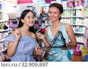 Girl and mother trying face powder and mirror at cosmetics shop. Стоковое фото, фотограф Яков Филимонов / Фотобанк Лори