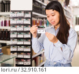 Young Asian girl choosing pack of false eyelashes. Стоковое фото, фотограф Яков Филимонов / Фотобанк Лори