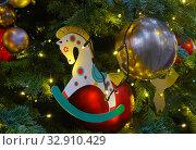 Купить «Игрушечная лошадка и шары украшают елку», фото № 32910429, снято 5 января 2020 г. (c) Наталья Николаева / Фотобанк Лори