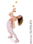 Young sweet woman in pajamas and slippers juggles tangerines. Стоковое фото, фотограф Алексей Кузнецов / Фотобанк Лори