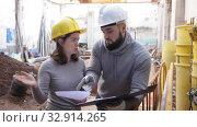 Купить «Two confident engineers discussing blueprint while standing at construction site», видеоролик № 32914265, снято 11 декабря 2019 г. (c) Яков Филимонов / Фотобанк Лори