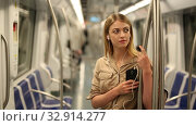 Купить «Young woman with a smartphone and headphones enters a subway car», видеоролик № 32914277, снято 31 марта 2019 г. (c) Яков Филимонов / Фотобанк Лори