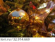 Купить «Новогодние елочные украшения. На елке висит большая лучистая звезда, в которой отражается соседний шар», фото № 32914669, снято 5 января 2020 г. (c) Наталья Николаева / Фотобанк Лори