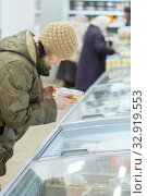 Купить «Russia Samara November 2019: A mature woman is standing in a store near the refrigerator, is holding a package with a semi-finished product in her hands and is looking at the price.», фото № 32919553, снято 13 ноября 2019 г. (c) Акиньшин Владимир / Фотобанк Лори