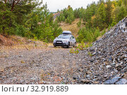 Russia, Bashkortostan, September 2019: Mitsubishi ASX crossover car overcomes a steep climb along a gravel road through the forest. Редакционное фото, фотограф Акиньшин Владимир / Фотобанк Лори
