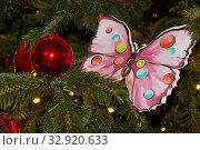 Купить «Украшения новогодней елки: шар, светящиеся лампочки и бабочка», фото № 32920633, снято 5 января 2020 г. (c) Наталья Николаева / Фотобанк Лори