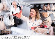 Купить «Smiling young woman customer choosing bras», фото № 32920977, снято 20 марта 2017 г. (c) Яков Филимонов / Фотобанк Лори