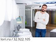 Купить «Positive man buyer choosing ceramic washbasin in shop», фото № 32922105, снято 2 февраля 2018 г. (c) Яков Филимонов / Фотобанк Лори