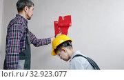 Купить «Apartment renovation - covering roller in paint and painting walls in red color», видеоролик № 32923077, снято 3 июня 2020 г. (c) Константин Шишкин / Фотобанк Лори