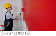 Apartment renovation - a little boy in helmet and glasses painting wall in red. Стоковое видео, видеограф Константин Шишкин / Фотобанк Лори