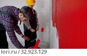 Купить «Apartment renovation - father and son covering roller in red paint», видеоролик № 32923129, снято 3 июня 2020 г. (c) Константин Шишкин / Фотобанк Лори