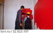 Купить «Apartment renovation - family of father and son covering wall in red paint», видеоролик № 32923197, снято 3 июня 2020 г. (c) Константин Шишкин / Фотобанк Лори