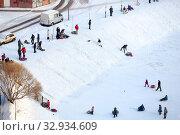 Families with adults and kids sled from slope on a snowy day. Санкт-Петербург (2013 год). Редакционное фото, фотограф Кекяляйнен Андрей / Фотобанк Лори